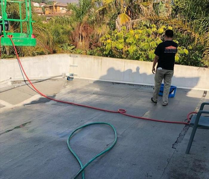 Roof of home in Malibu being cleaned by SERVPRO technician
