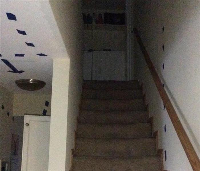 tape on wall and ceiling to mark water damage on staircase