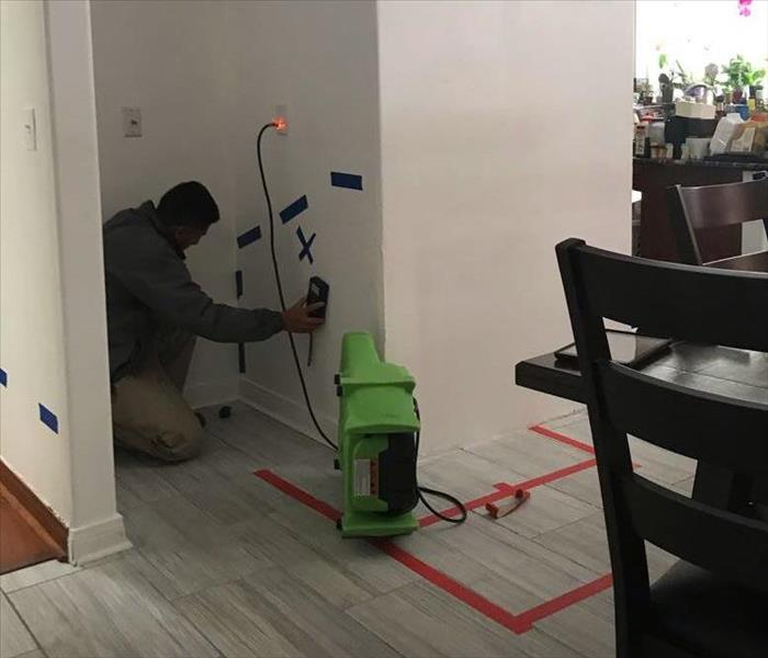 Drying equipment placed in kitchen with man using moisture meter on wall