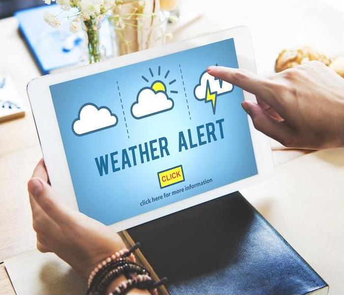person on a white tablet using weather alert app
